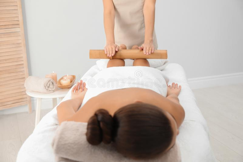 Young woman having massage with bamboo stick. In wellness center royalty free stock photo