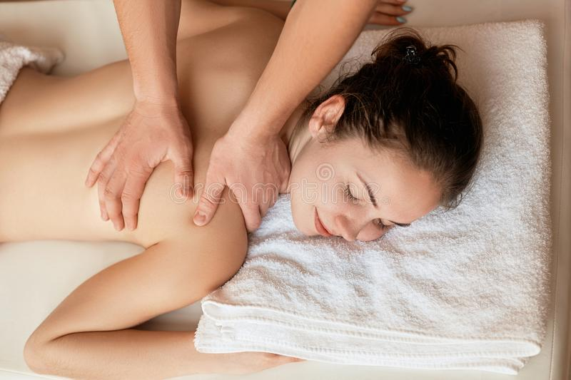 Young woman having massage in spa salon. Body care. Spa body massage stock images
