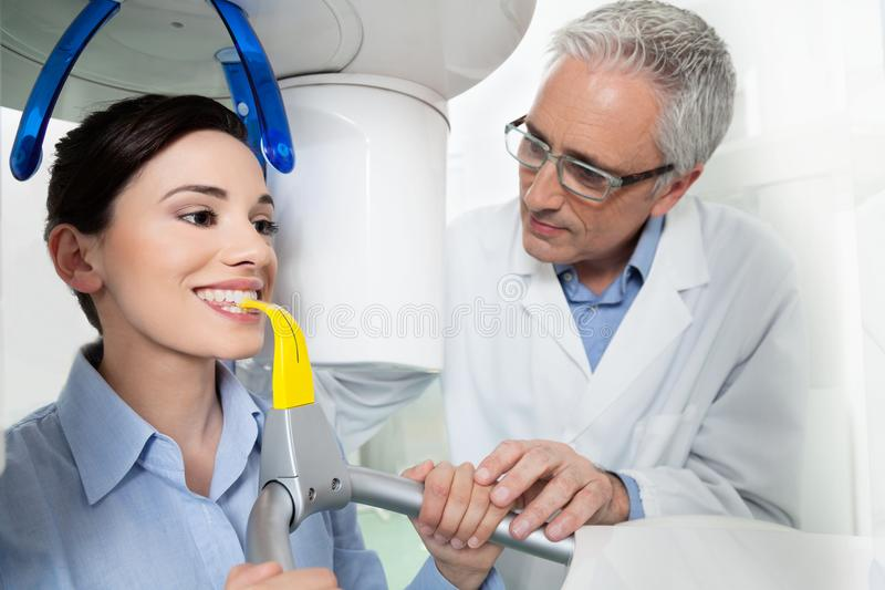 Young woman having panoramic digital X-ray with a the dentist. Young women portrait having panoramic digital X-ray of her teeth with a middle age doctor in the stock image