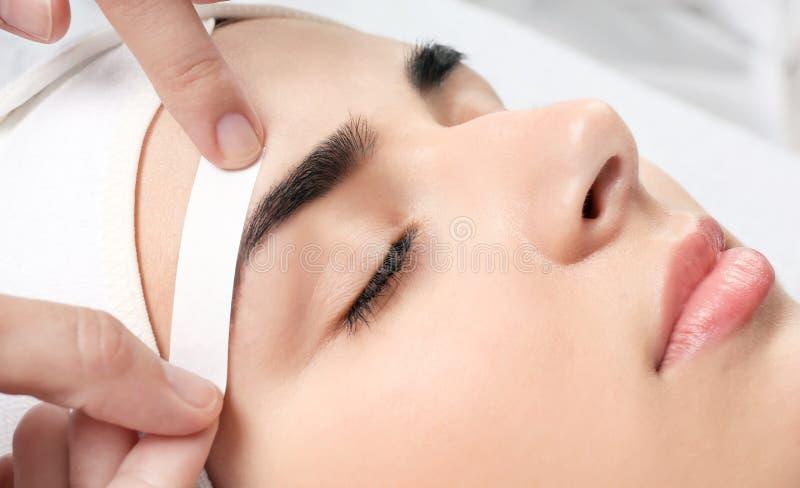 Young woman having professional eyebrow correction. Procedure in beauty salon, closeup stock photo