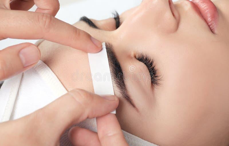 Young woman having professional eyebrow correction. Procedure, closeup stock photo