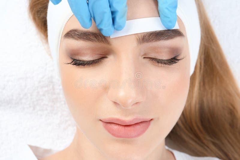Young woman having professional eyebrow correction. Procedure in beauty salon stock photos