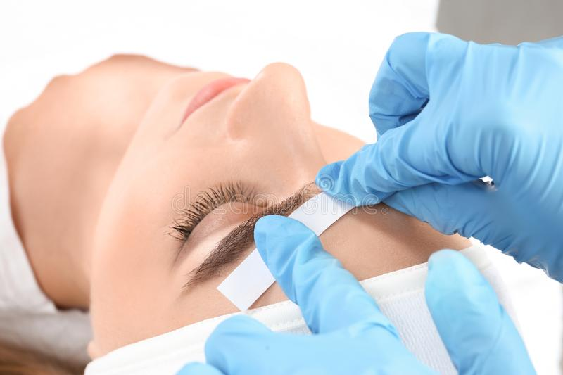 Young woman having professional eyebrow correction. Procedure in beauty salon stock photography