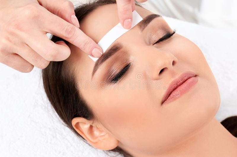 Young woman having professional eyebrow correction. Procedure in beauty salon royalty free stock photos