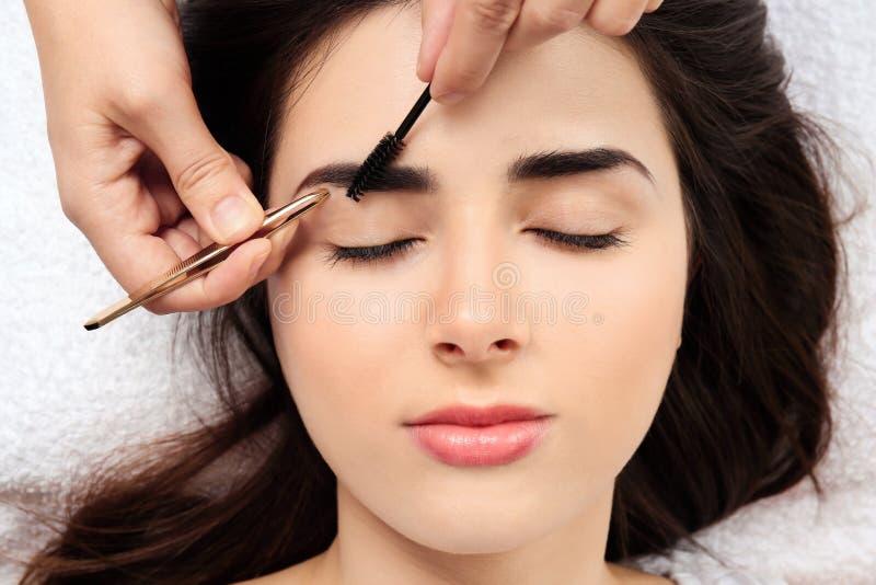 Young woman having professional eyebrow correction stock photo