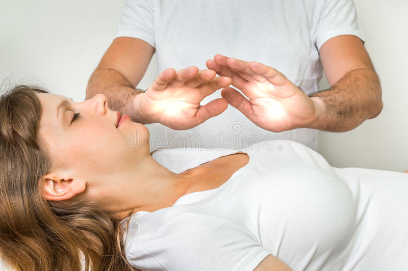 Young woman having reiki healing treatment stock photography