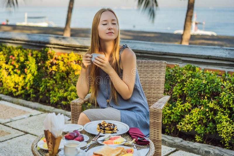 Young woman having romantic breakfast in sunrise at resort restaurant outdoor. Healthy food drink for breakfast stock photos
