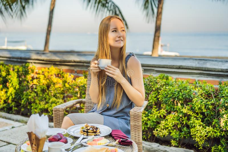 Young woman having romantic breakfast in sunrise at resort restaurant outdoor. Healthy food drink for breakfast royalty free stock photography