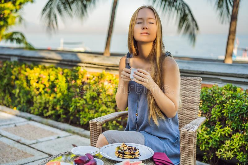 Young woman having romantic breakfast in sunrise at resort restaurant outdoor. Healthy food drink for breakfast stock images