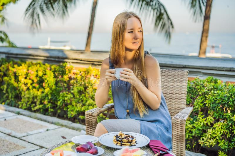 Young woman having romantic breakfast in sunrise at resort restaurant outdoor. Healthy food drink for breakfast stock photo