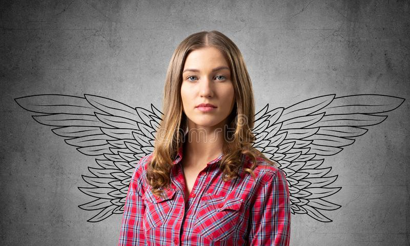 Young woman having serious and calm face. Angel wings illustration on grey wall. Caucasian brown haired girl has confident facial expression. Portrait of girl stock photography