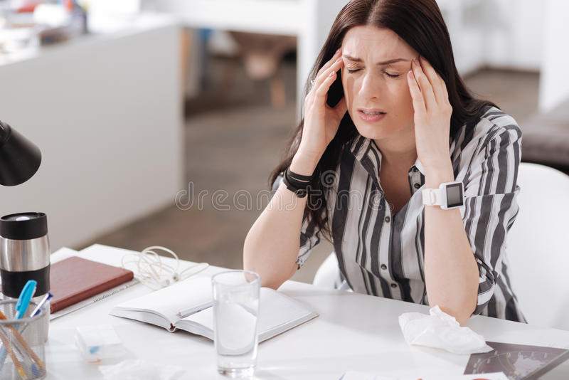 Young woman having terrible headache. Cannot bear such pain. Sick female holding elbows on the table wrinkling her forehead while touching temple royalty free stock photo