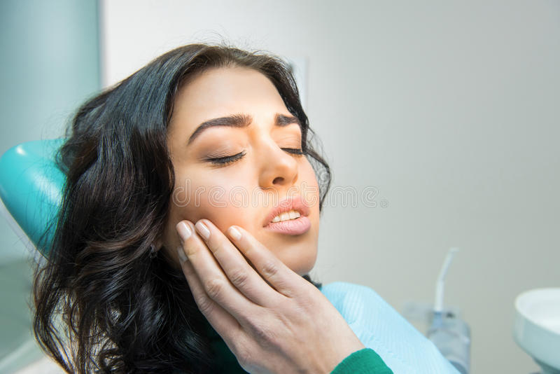 Young woman having toothache. Sad lady at the dentist. Gum disease symptom royalty free stock photo