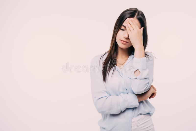 A young woman with a headache holding head, isolated on white stock image
