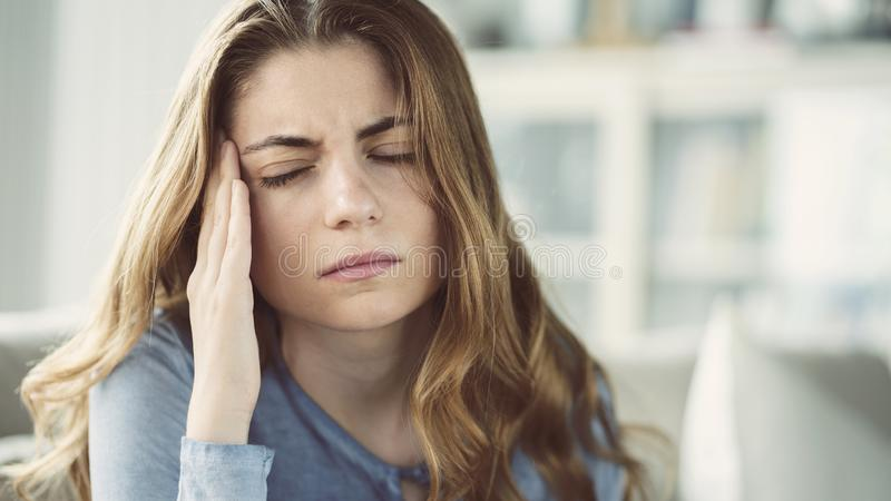 Young woman with headache in home interior. Young woman with headache in  home interior royalty free stock photos