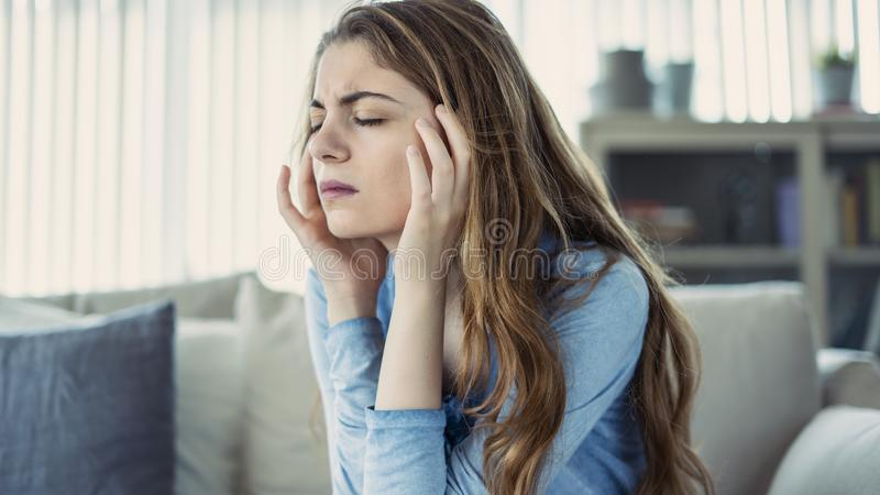 Young woman with headache in home. Young woman with headache  in home stock photography