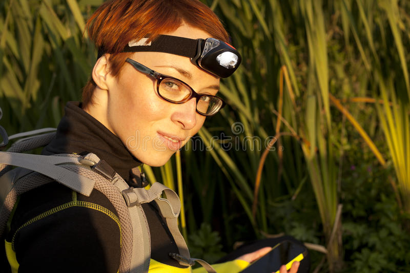Young woman with headlamp on head and digital compas looking for. Geocaching royalty free stock images