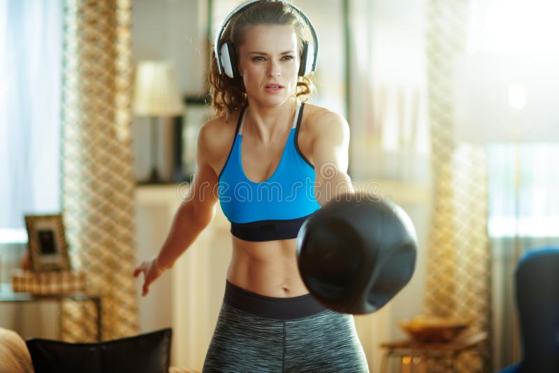 Young woman in headphones doing functional training workout. Young woman in headphones in sport clothes in the modern living room doing functional training royalty free stock image