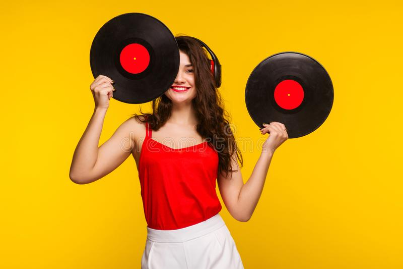 Young woman in headphones looking at camera and closing her face with vinyl record royalty free stock images