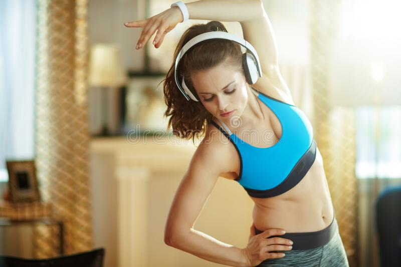 Young woman in headphones at modern home stretching. Young woman in headphones in fitness clothes at modern home stretching stock image