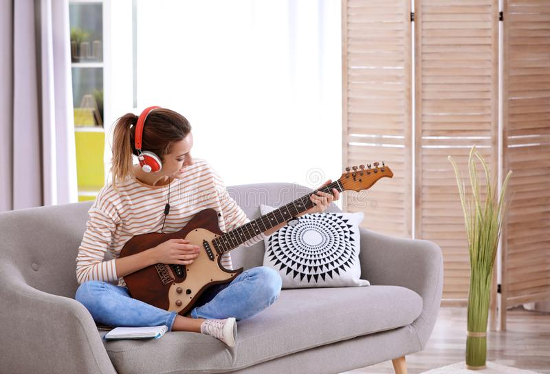 Young woman with headphones playing electric guitar in living room. stock photo