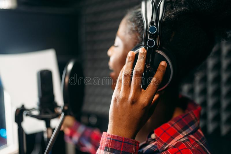 Young woman songs in audio recording studio stock photo
