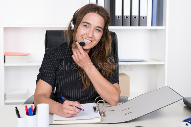 Young woman with headset is writing into a file royalty free stock image
