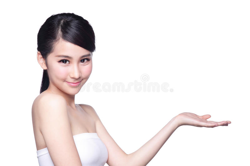 Young woman with health skin show. Beautiful young woman with healthy clean skin presenting something on her hand. Isolated on white. asian beauty stock images