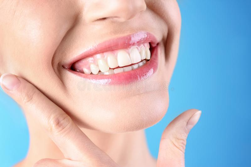 Young woman with healthy teeth and beautiful smile on color background. Closeup stock photo