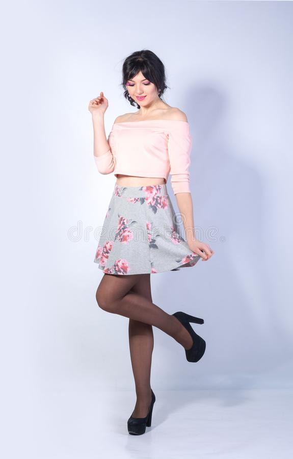 Young woman with a heart on her cheek in a mini skirt smiles on. Young playful woman with a heart on her cheek in a mini skirt smiles on a white background stock photo