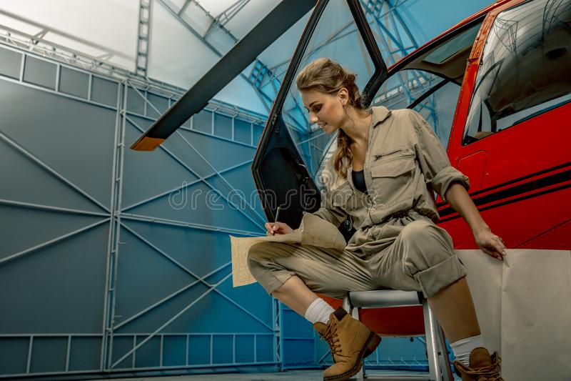 Young woman helicopter pilot or mechanic reading map. helicopter crash royalty free stock image
