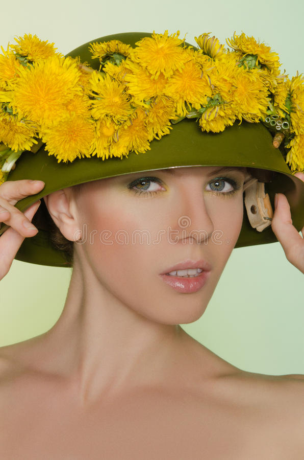 Young woman in helmet with a wreath of dandelions. Young woman in helmet with a wreath of yellow dandelions stock photos