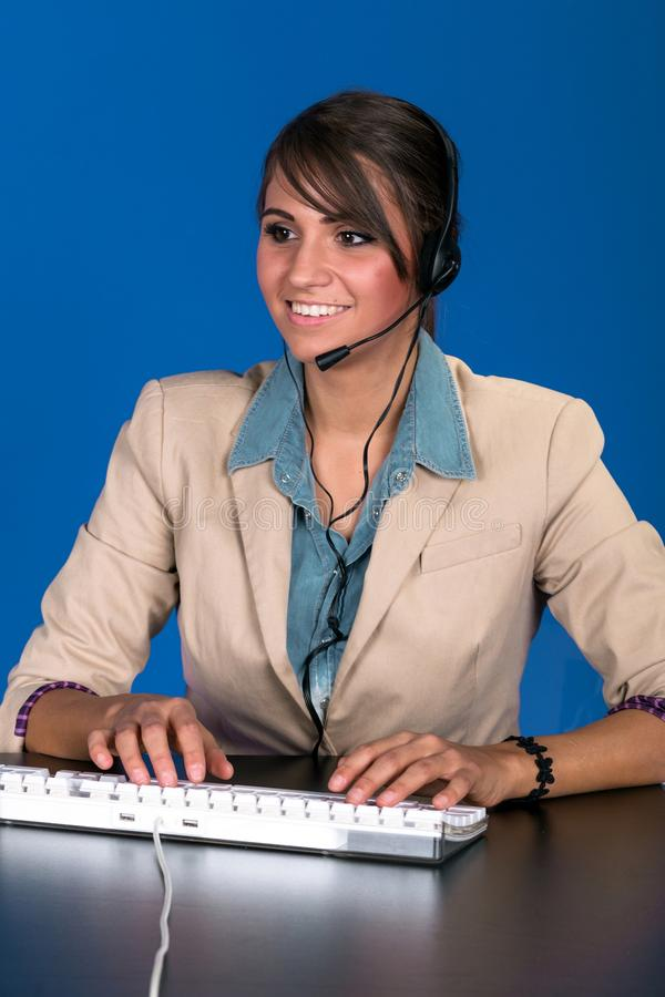 Young woman at the helpdesk. Against blue background stock images