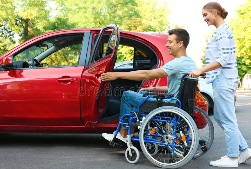 Young woman helping disabled man in wheelchair to get into car royalty free stock photo