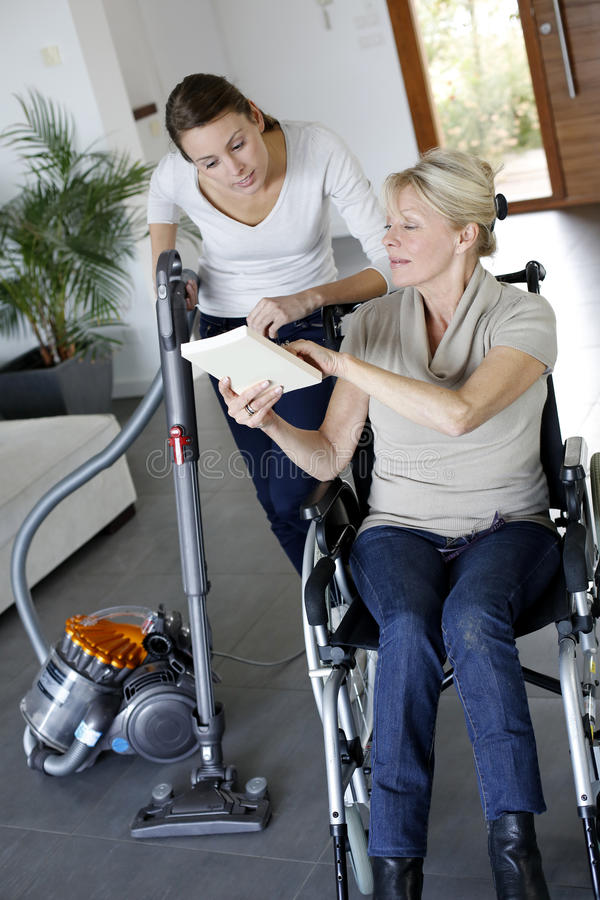 Young woman helping disabled woman at home royalty free stock photos