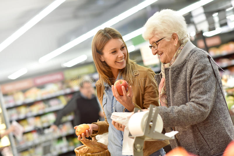 Young woman helping elderly with groceries stock images
