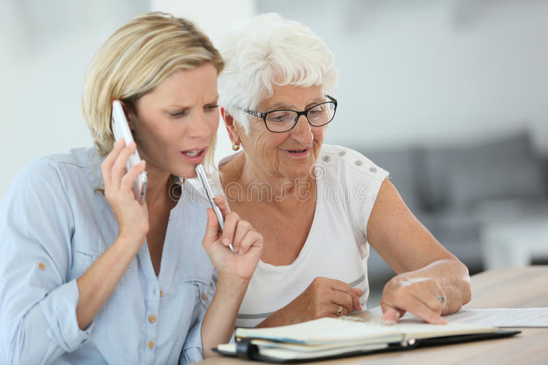 Young woman helping elderly woman with appointments stock images