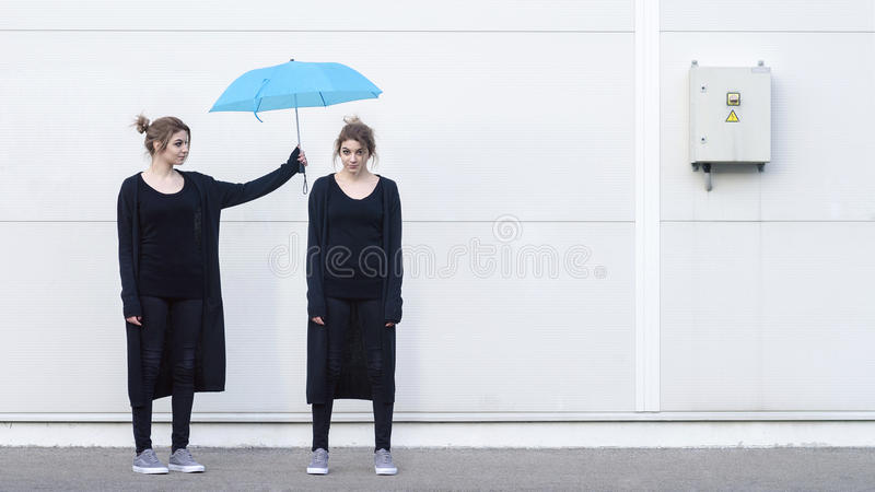 Young woman helping herself design concept. Young woman helping herself with blue umbrella design concept stock photography