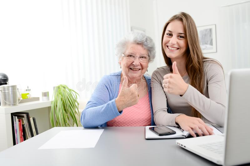 Young woman helping an old senior woman doing paperwork and administrative procedures with laptop computer at home. Young women helping an old senior women doing stock photo