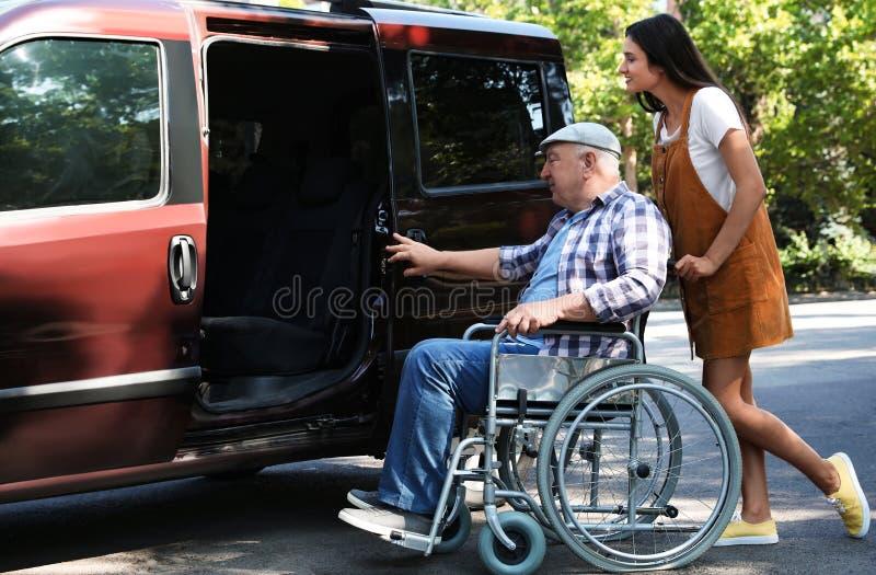 Young woman helping senior man in wheelchair to get into van. Young women helping senior men in wheelchair to get into van outdoors royalty free stock photos