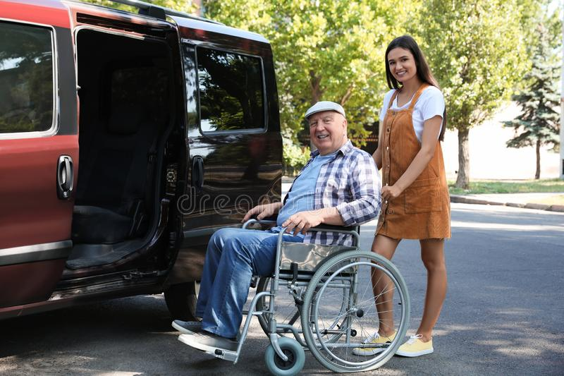 Young woman helping senior man in wheelchair to get into van. Young women helping senior men in wheelchair to get into van outdoors stock image