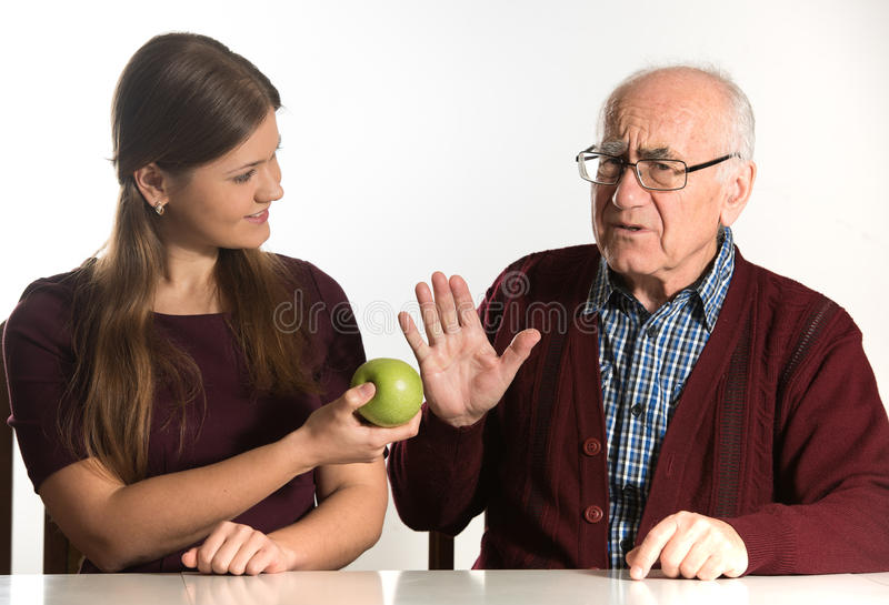 Young woman helps senior man. Young women helps senior men to eat green apple stock photos