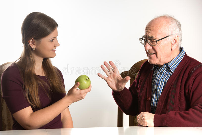 Young woman helps senior man. Young women helps senior men to eat green apple royalty free stock photo