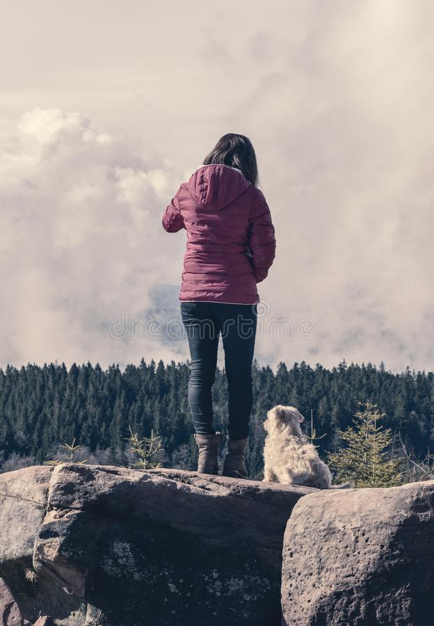 Millennial girl and her dog on mountain rocks looking in the distance stock image