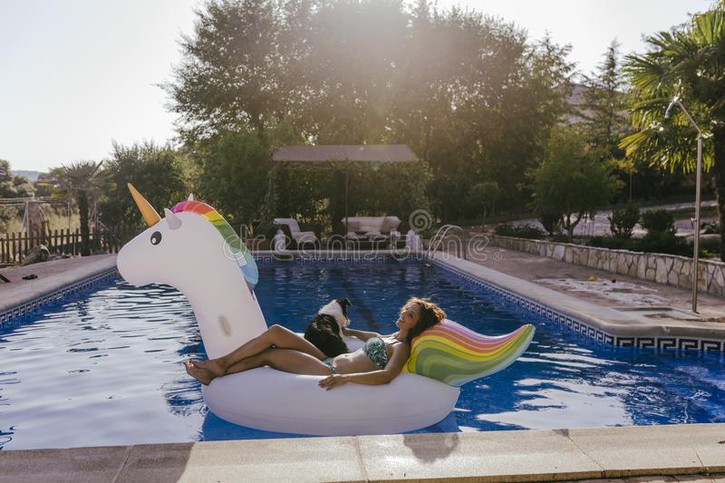 young woman and her border collie dog standing on an inflatable toy unicorn at the swimming pool. Summertime, fun and lifestyle royalty free stock images