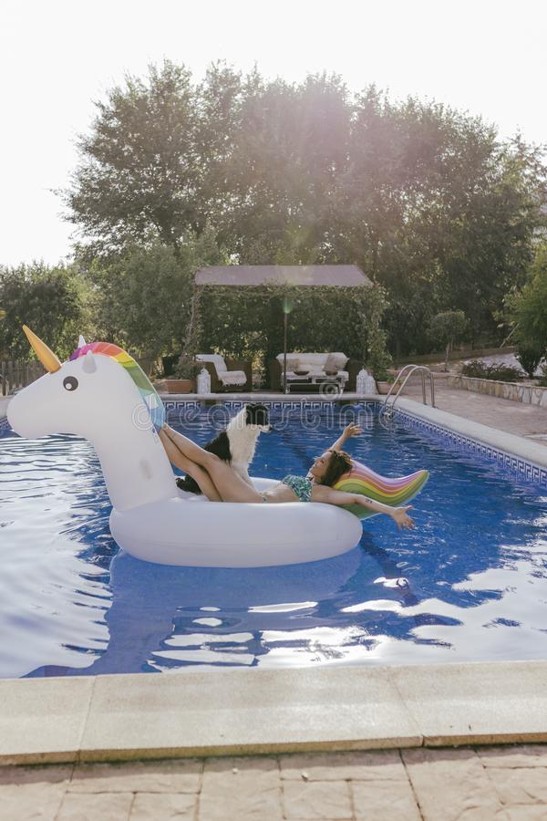 Young woman and her border collie dog standing on an inflatable toy unicorn at the swimming pool. Summertime, fun and lifestyle royalty free stock photo