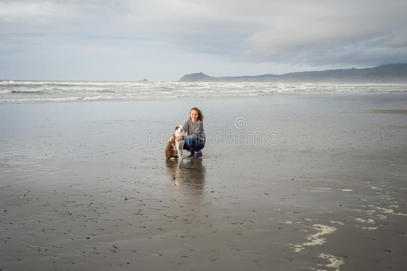 Young woman and her Border Collie dog together on a Northern California beach royalty free stock image