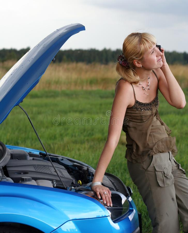 Young woman and her broken car stock image