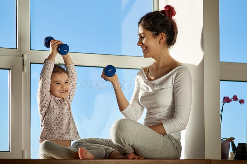 Young woman with her child holding a dumbbell and doing sports. Her daughter with a proud expression lifts the dumbbell stock photography