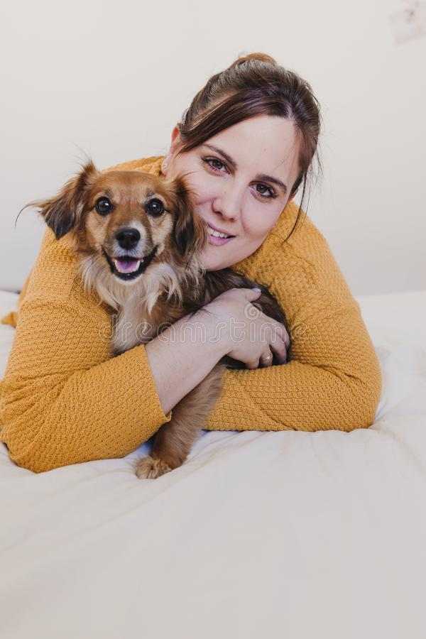 Young woman and her cute dog sitting on bed. love for animals concept. top view. Young woman and her cute dog sitting on bed. love for animals concept. Hug royalty free stock photos